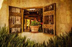 Flowers in the window of adobe style house. Adobe style house with wooden shutters and flowers in the window Royalty Free Stock Photo
