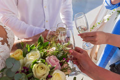 Flowers and wine glasses in the hands Stock Photography