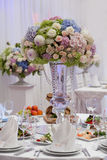 Flowers, wine glasses, napkins and salad on the table. Royalty Free Stock Photography