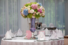 Flowers, wine glasses, napkins and salad on the table. Royalty Free Stock Image