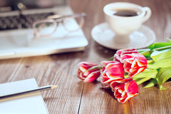 Flowers on wood table. cup of coffee and laptop on background Stock Image