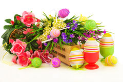 Flowers in wooden basket with easter eggs Stock Images