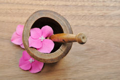 Flowers in wooden pestle for aromatherapy and spa. Flowers in a pestle for aromatherapy and spa on a wooden background Royalty Free Stock Photography