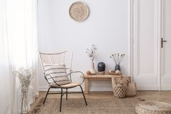 Flowers on wooden stool next to armchair in white loft interior with pouf and plate. Real photo stock photography