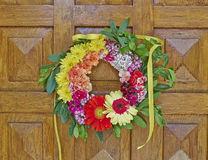 Flowers wreath hanging on wooden door Royalty Free Stock Photo