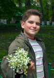 Flowers for you. The boy stretches flowers Royalty Free Stock Photos