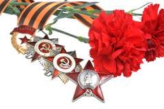 Flowerss ató con la cinta de San Jorge, órdenes de la gran guerra patriótica Imagen de archivo libre de regalías