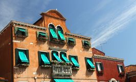 Flowery balcony in Venetian style with Windows and green awnings Royalty Free Stock Photos