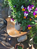 Flowery Farm Greeting Card. Colorful pansies on an old medal saddle chair Royalty Free Stock Photos