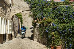 Flowery roadin ancient city. Motor cyclist on the narrow street in the ancient city of Rhodes, Rhodes island, Greece. 29.06.2014 Royalty Free Stock Images