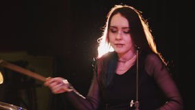Flowing black hair - beauty girl plays drum rock at garage. Close up royalty free stock images