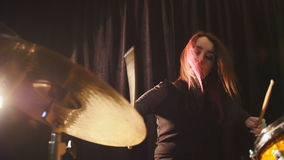 Flowing black hair - beauty girl plays drum rock at garage. Close up royalty free stock photo