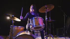Flowing black hair - beauty girl plays drum rock at garage Royalty Free Stock Photos