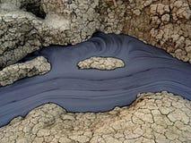 The volcano mud spring. Flowing black mud river in Berca mud volcanoes in Romania Royalty Free Stock Images