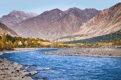 Flowing blue water of Gilgit River with mountains in the background. Pakistan. stock photos