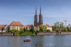 Flowing boat on the river and a view of Ostrow Tumski. Wroclaw, Poland royalty free stock photography