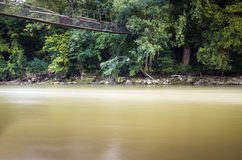 Flowing dirty river under old ruined cable bridge. Flowing dirty river under old cable bridge Royalty Free Stock Photos