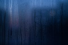 Flowing down water drops on window glass Royalty Free Stock Image
