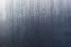 Flowing down water drops on window glass Stock Images