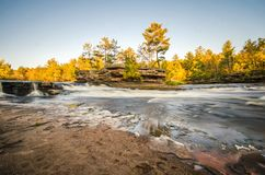 Flowing Kettle River in Banning State Park in Minnesota during the fall. Long exposure. Flowing Kettle River in Banning State Park in Minnesota on a sunny fall stock photos