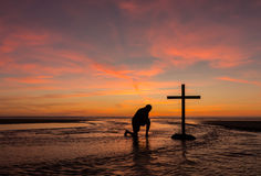 Flowing Prayers. A man praying by a black cross with a flowing stream water around it, at a beach with the sunset sky Stock Photos