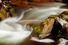 Flowing river blurred through rocks Stock Photo