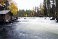 Flowing river flow and aged unemployed watermill Royalty Free Stock Photo