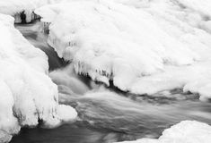 Flowing river and icicles in winter royalty free stock image