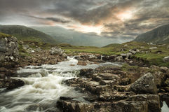 A flowing river with a mountain backdrop Royalty Free Stock Photo