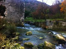 Flowing river by the old mill. Flowing river over the stones by the abandoned mill in Croatia Royalty Free Stock Images