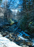 Flowing River beside Snowbank Stock Image