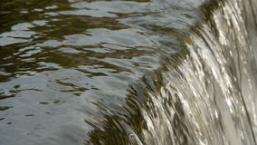 Flowing river water close-up. Peaceful flowing water in the river close-up. A small waterfall. Falling water lather stock footage