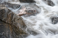 Flowing by the Rocks. The water stream is flowing by the stable rocks royalty free stock images