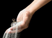Flowing sand and running time. Sand flowing between fingers of a hand holding an antique pocket watch Royalty Free Stock Photo