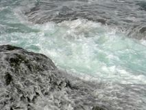 Flowing sea water. Sea water rushes into a channel between ocean rocks Royalty Free Stock Photo