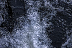Flowing and sparkling dark water. Close view of a flowing and sparkling dark water Royalty Free Stock Photography