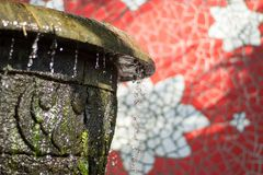 Flowing splashing close up water fountain with summer sunlight stock images