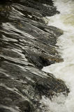Flowing stream. Scenic view of stream flowering over rocks with motion blue and white water Royalty Free Stock Images