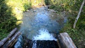 Flowing stream in gutter. Clear mountain stream flowing from wooden gutter stock video footage