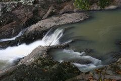 Flowing Stream Murky. A flowing Murky stream with small waterfalls Stock Photo