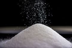 Flowing sugar forming a pile as it falls Royalty Free Stock Photo