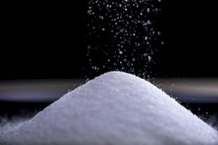 Flowing sugar forming a pile as it falls Royalty Free Stock Photography