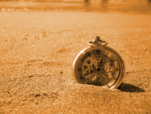 Flowing of time. An old clock on a beach near the shore royalty free stock images