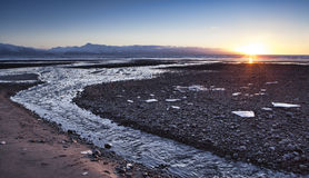 Flowing to the Sea. Water flowing to the sea on an Alaskan beach at sunset with some ice chunks in the foreground and a blue sky Royalty Free Stock Image