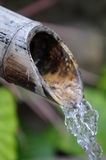 Flowing water. Water flowing out of a bamboo fountain Stock Photo