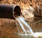 Flowing water. Beautiful shot of water flowing from metal pipe Stock Photos