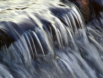 Flowing water. Taken with a slow shutter speed in a river stream Royalty Free Stock Photos