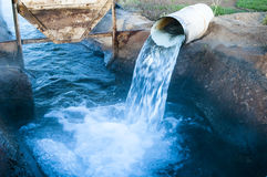 Flowing water. Water flowing from a pipe into an irrigation canal Stock Photography