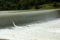 Flowing water. Water flowing alone the edge of a weir royalty free stock photo