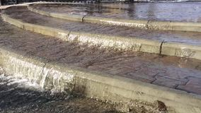 Flowing water on asphalt road after rain storm. Close up flowing water on asphalt road after rain storm stock footage